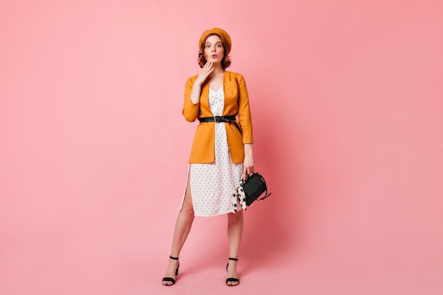 Full length view of jocund french lady with handbag. studio shot of trendy slim girl in yellow beret.