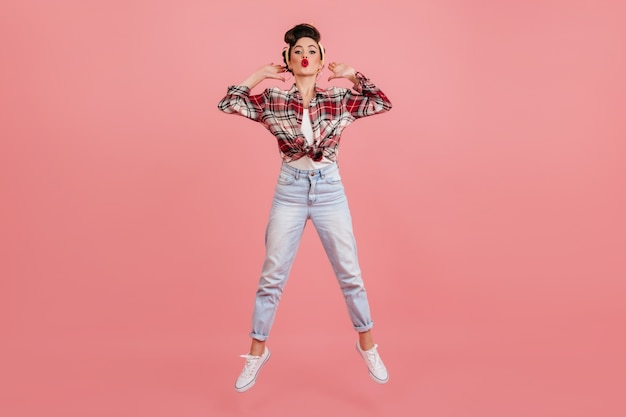 Full length view of jumping pinup girl. studio shot of woman in jeans and checkered shirt posing on pink background.