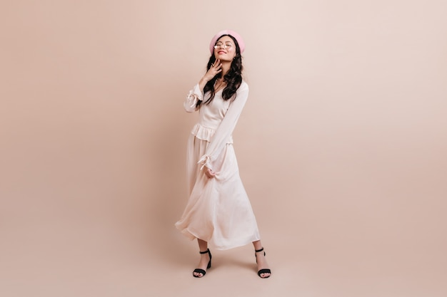 Vista integrale della ragazza coreana in berretto. elegante modello asiatico in posa su sfondo beige.