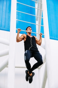 Full length view of motivated strong sportsman doing pull ups listening to music