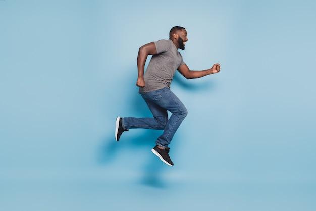 Вид в полный рост афро-парня, прыгающего на синем фоне