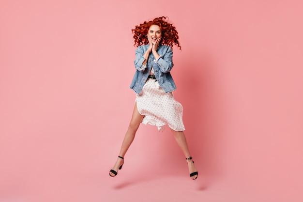 ピンクの背景にジャンプする驚いた生姜の女性の完全な長さのビュー。デニムジャケットとハイヒールの靴でアクティブな巻き毛の女の子のスタジオショット。
