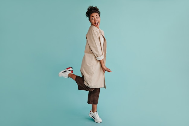 片足で立っているトレンチコートの素晴らしい女性の完全な長さのビュー