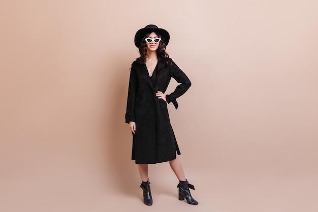 黒のコートでアジアの女性の完全な長さのビュー。ベージュの背景に立っている自信を持って韓国人女性のスタジオショット。