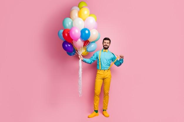 Вид в полный рост привлекательного веселого парня, держащего воздушные шары, тянущего за подтяжки