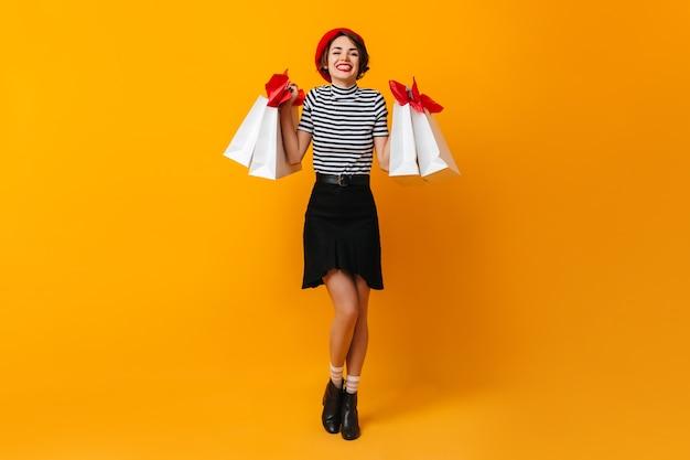 Вид в полный рост красивой брюнетки с магазинными сумками