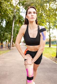 Вид в полный рост красивой подходящей девушки в черной спортивной одежде, тренирующейся в летнем парке, в кинезиологических эластичных лентах.