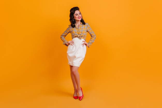 Вид в полный рост красивой женщины в белой юбке, стоя в позе уверенно. утонченная девушка кинозвезды позирует с оружием подбоченясь на желтом фоне.