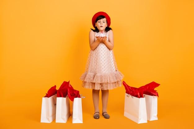 買い物の後にポーズをとる誕生日の少女の全身像。子供はケーキにろうそくを吹き消します。