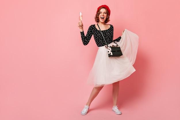 치마를 가지고 노는 명랑 한 프랑스 여자의 전체 길이보기. 분홍색 배경에 와인 잔을 들고 베레모에 행복 곱슬 여자.