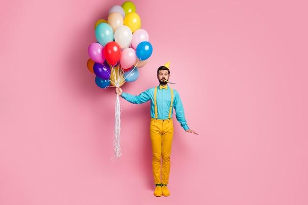 Полный вид комического бородатого парня, держащего воздушные шары, дующий в свисток