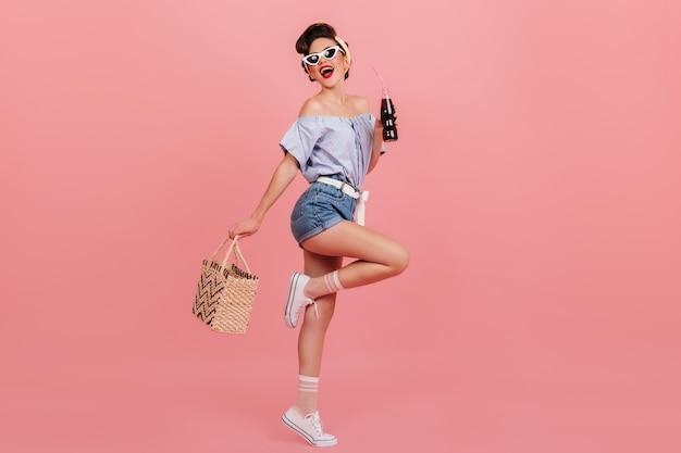 Полный вид танцующей девушки кинозвезды. студия выстрел изящной молодой женщины с бутылкой напитка и сумкой.