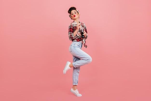 踊るピンナップガールの全身像。ソーダを飲むスタイリッシュなブルネットの女性。