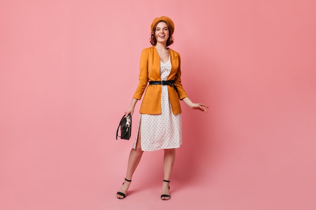黄色のジャケットでフランス人女性の全身像。ピンクの背景の上に立っているハンドバッグを持つエレガントな女の子のスタジオショット。