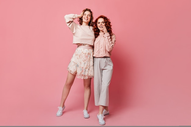 友人とポーズをとってスカートの女の子の完全な長さのビュー。ピンクの背景の上に立っている2人のスタイリッシュな若い女性のスタジオショット。