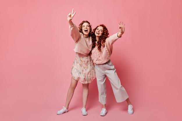 평화와 괜찮은 징후를 보여주는 여자의 전체 길이보기. 분홍색 배경에 몸짓 웃는 친구의 스튜디오 샷.