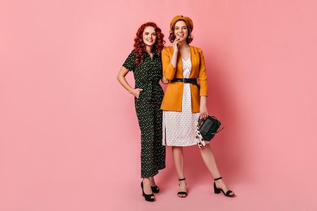 굽 높은 신발에 화려한 숙녀의 전체 길이보기. 분홍색 배경에 서 우아한 여자 친구의 스튜디오 샷.