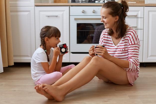 Вид в полный рост счастливой матери, пьющей чай из чашек со своей улыбающейся дочерью, семьи, сидящей на полу кухни, завтракающей и проводящей выходные вместе дома