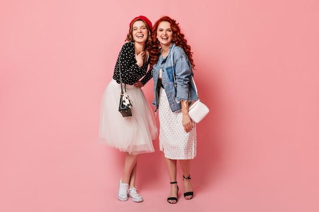 카메라를 비웃는 행복 자매의 전체 길이보기. 미소와 분홍색 배경에 포즈 유행 여자의 스튜디오 샷.