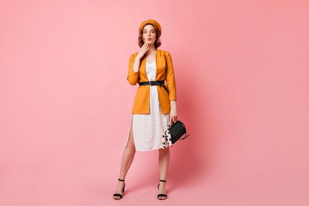ハンドバッグとjocundフランスの女性の完全な長さのビュー。黄色いベレー帽の流行のスリムな女の子のスタジオショット。