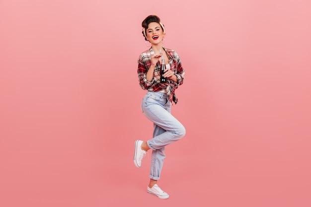 ジーンズのピンナップガールの全身像。ソーダボトルでポーズをとって笑っているエレガントな女性のスタジオショット。