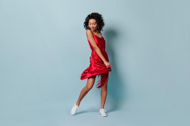Вид в полный рост игривой молодой женщины, танцующей на синей стене