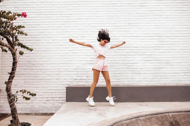 通りをジャンプして喜んでいる女性の完全な長さのビュー。ショートパンツで魅力的な日焼けした女性の屋外ショット。
