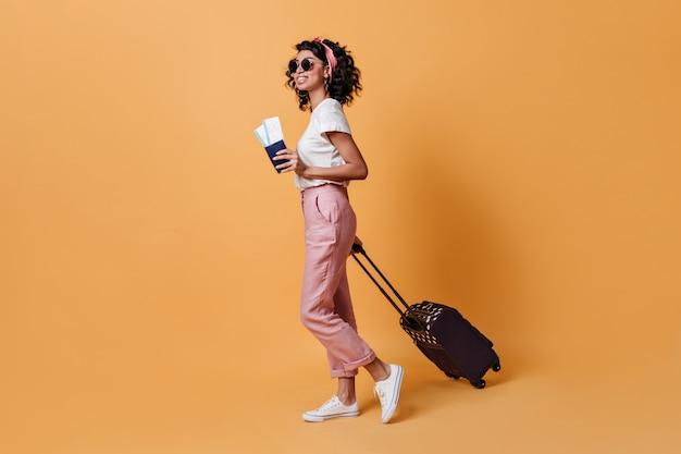 スーツケースを持つかなり若い女性の全身像