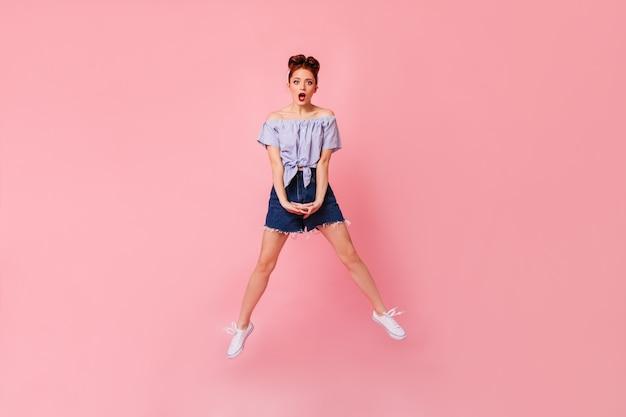 デニムのショートパンツとブラウスでショックを受けた女性の全身像。ピンクの空間にジャンプする驚いたピンナップガールのスタジオショット。