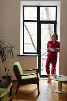 아침에 잡지를 읽고 웃는 유럽 여자의 전체 길이보기. 창 근처에 서있는 파자마에 사랑스러운 맨발의 여자의 실내 샷.