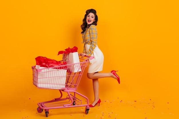 노란색 배경에 포즈 멋진 여성 구매자의 전체 길이보기. 카메라를보고 우아한 핀 업 소녀입니다.