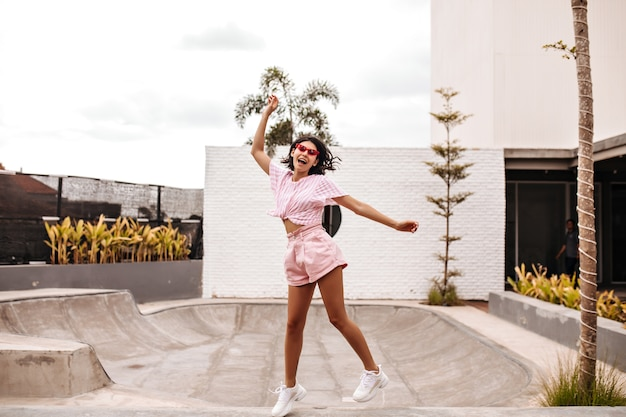 通りをジャンプするショートパンツで日焼けした女性の完全な長さのビュー。夏を楽しんでいるヨーロッパの女性の屋外ショット。