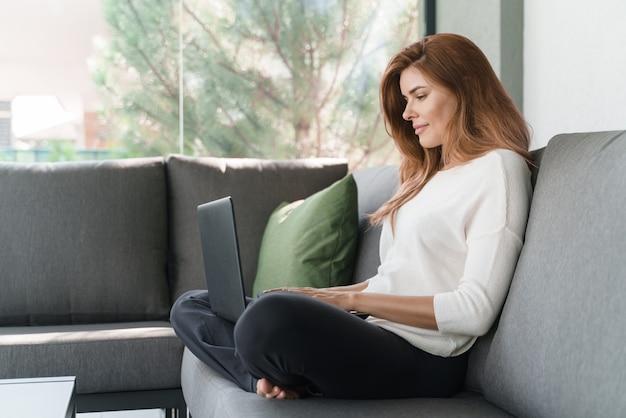 노트북을 사용하여 온라인으로 친구와 채팅하거나 소파에 앉아 새 프로젝트에서 작업하는 쾌활한 예쁜 여성의 전체 길이 보기. 스톡 사진