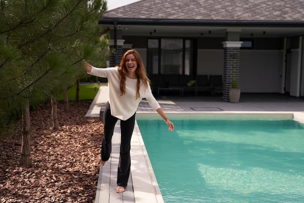 현대적인 빌라의 수영장 근처에서 시간을 보내는 동안 기뻐하는 행복한 여성의 전체 길이 보기. 아침에 기분이 좋은 생강 여자