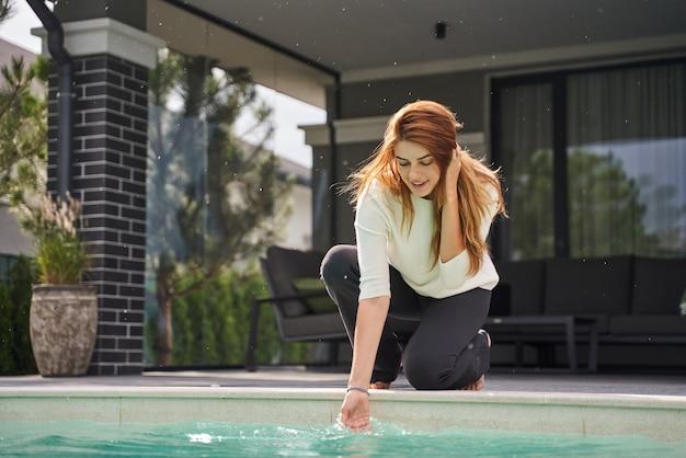 수영장 근처 바닥에 앉아서 물을 가지고 노는 행복한 여자의 전체 길이 보기. 물에 손을 넣어 생강 소녀