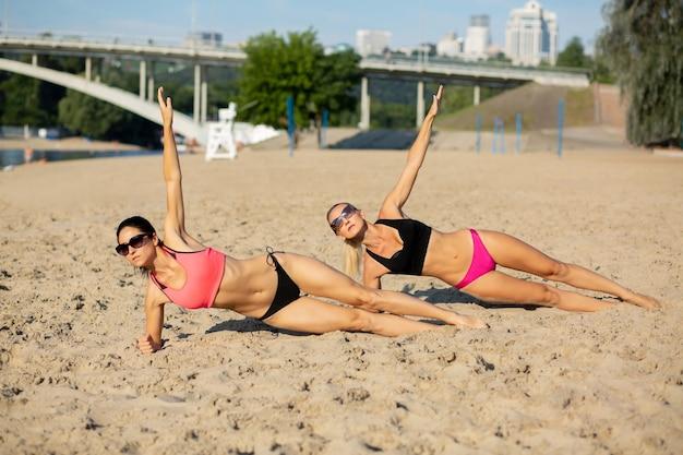ビーチでサイドプランクの位置にある2人の強い運動の女の子の完全な長さのビュー