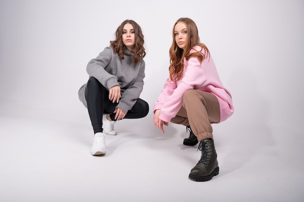 Две молодые девушки в модной спортивной одежде сидят на корточках в полный рост