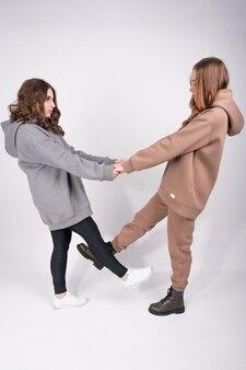 Две молодые стильные девушки в модной повседневной одежде в полный рост держатся за руки и смотрят друг на друга. концепция женского капсульного шкафа.