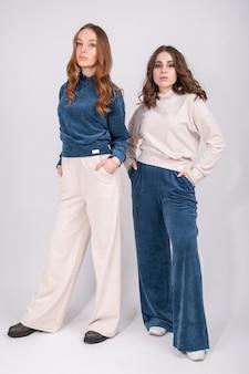 Две молодые стильные девушки в модной повседневной одежде в полный рост