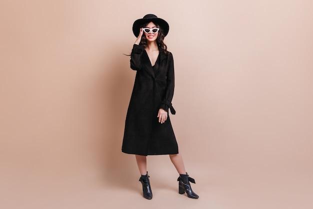 帽子とサングラスをかけた女性の全身像。ベージュの背景に立っているコートのエレガントなブルネットの女性。