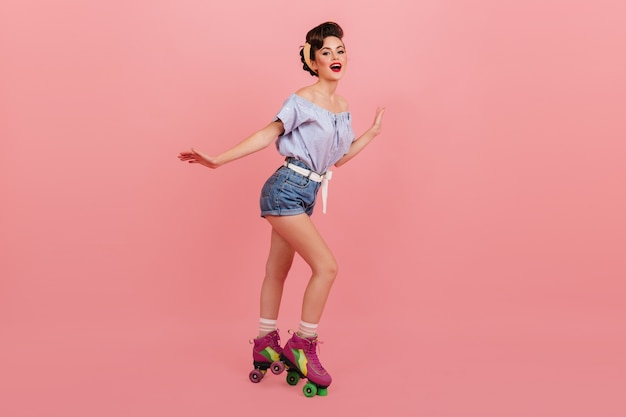 ローラースケートの女性の全身像。デニムのショートパンツでスリムなピンナップガールのスタジオショット。