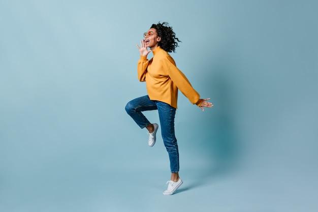 Вид в полный рост женщины, прыгающей на синей стене