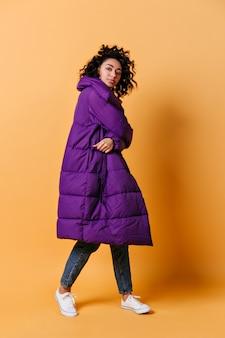 긴 다운 재킷에 젊은 여자의 전체 길이보기