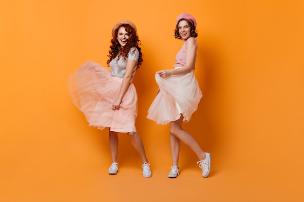 Full length view of romantic girls in skirts. studio shot of winsome curly women dancing on yellow background.