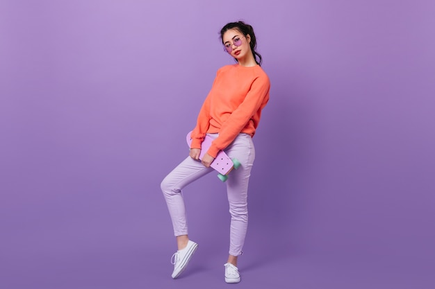 Full length view of stylish asian woman in glasses. winsome korean model holding skateboard on purple background.