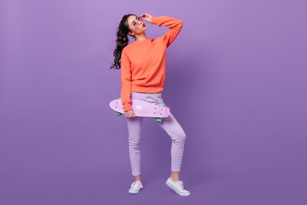 Vista integrale della ragazza coreana alla moda con lo skateboard. studio shot di splendida donna asiatica holding longboard su sfondo viola.