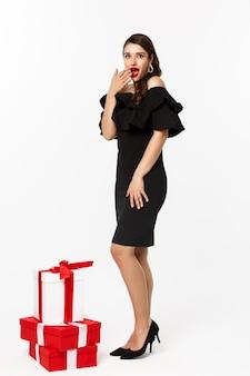 Vista integrale della donna in abito elegante e labbra rosse, che sembra sorpresa, riceve regali durante le vacanze di natale, in piedi con regali su sfondo bianco.