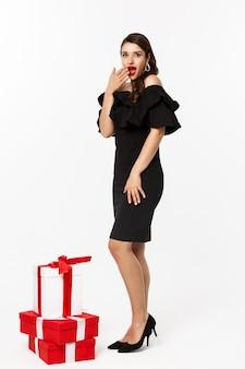 Vista a tutta lunghezza della donna in abito elegante e labbra rosse, che sembra sorpresa, riceve regali durante le vacanze di natale, in piedi con regali su sfondo bianco