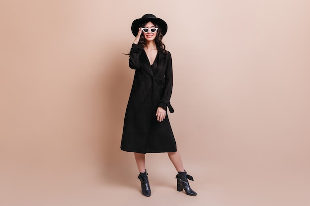 Full length view of woman in hat and sunglasses. elegant brunette woman in coat standing on beige background.