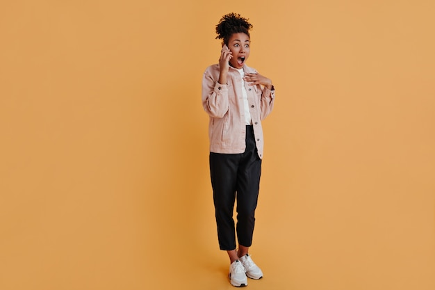 Full length view of woman talking on smartphone